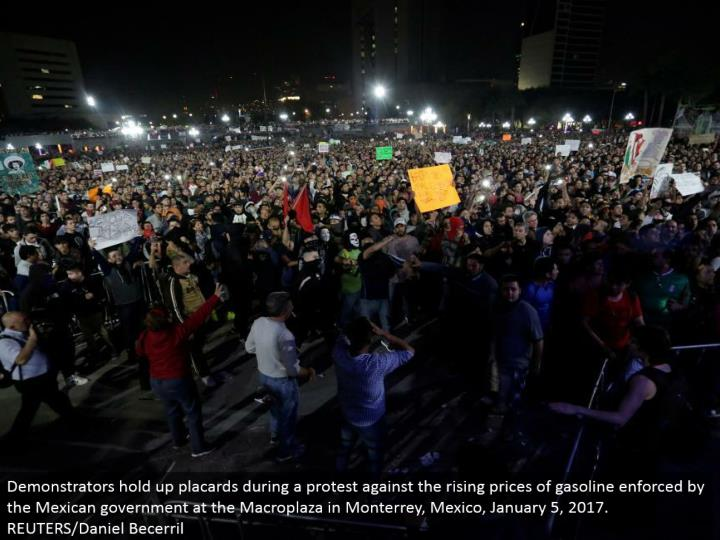 Demonstrators hold up notices amid a dissent against the rising costs of gas upheld by the Mexican government at the Macroplaza in Monterrey, Mexico, January 5, 2017. REUTERS/Daniel Becerril