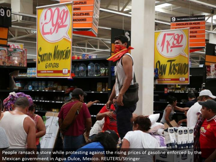 People scour a store while challenging the rising costs of fuel authorized by the Mexican government in Agua Dulce, Mexico. REUTERS/Stringer