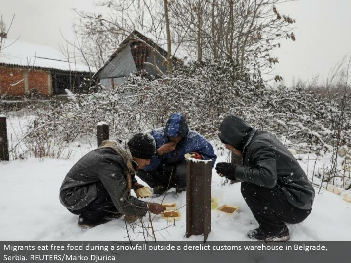 Migrants eat free nourishment amid a snowfall outside a neglected traditions distribution center in Belgrade, Serbia. REUTERS/Marko Djurica