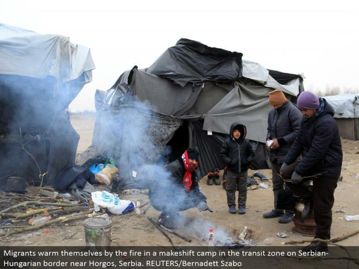 Migrants warm themselves by the fire in an improvised camp in the travel zone on Serbian-Hungarian outskirt close Horgos, Serbia. REUTERS/Bernadett Szabo