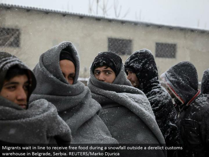 Migrants hold up in line to get free sustenance amid a snowfall outside an abandoned traditions distribution center in Belgrade, Serbia. REUTERS/Marko Djurica