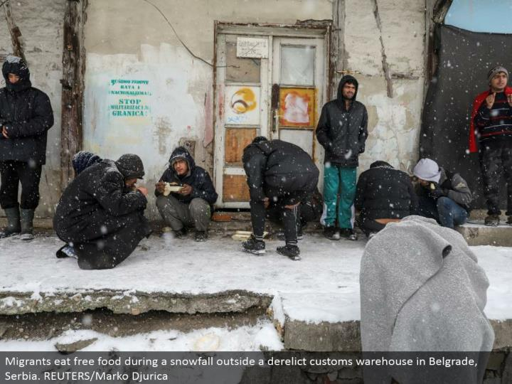 Migrants eat free nourishment amid a snowfall outside an abandoned traditions stockroom in Belgrade, Serbia. REUTERS/Marko Djurica