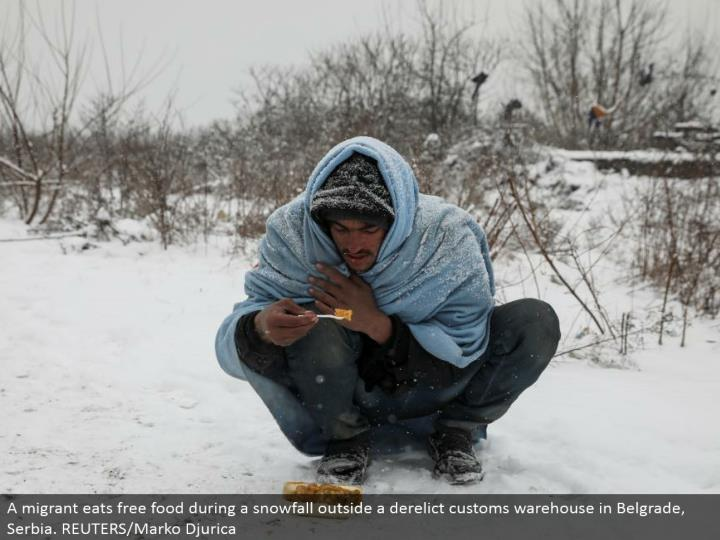A transient eats free sustenance amid a snowfall outside a forsaken traditions distribution center in Belgrade, Serbia. REUTERS/Marko Djurica