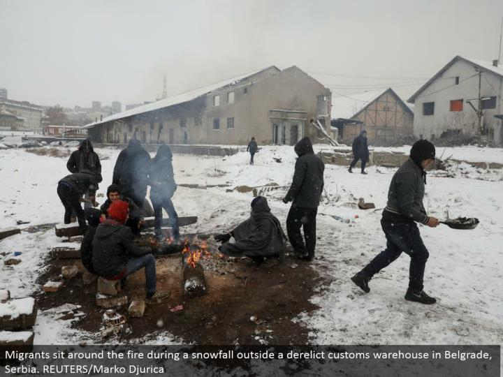 Migrants lounge around the fire amid a snowfall outside a forsaken traditions distribution center in Belgrade, Serbia. REUTERS/Marko Djurica