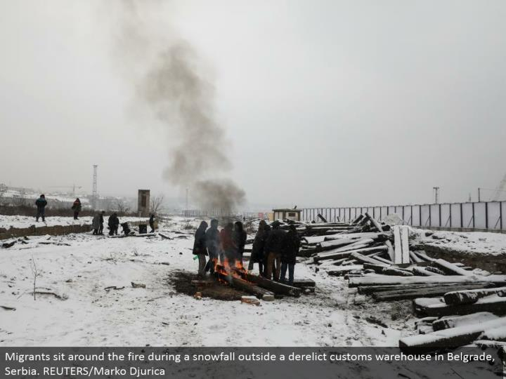 Migrants lounge around the fire amid a snowfall outside an abandoned traditions distribution center in Belgrade, Serbia. REUTERS/Marko Djurica