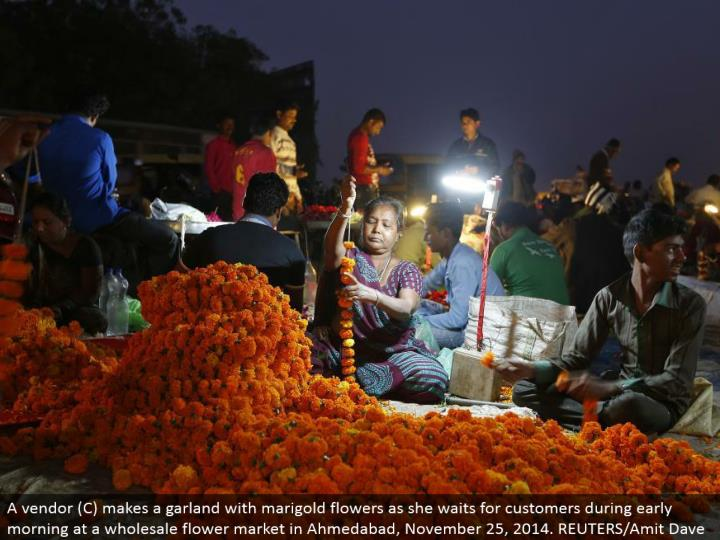 A merchant (C) makes a festoon with marigold blooms as she sits tight for clients amid early morning at a discount blossom advertise in Ahmedabad, November 25, 2014. REUTERS/Amit Dave