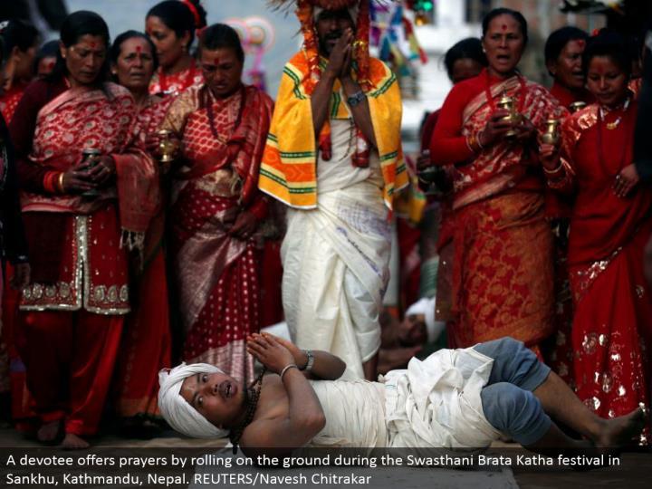A fan offers petitions by moving on the ground amid the Swasthani Brata Katha celebration in Sankhu, Kathmandu, Nepal. REUTERS/Navesh Chitrakar