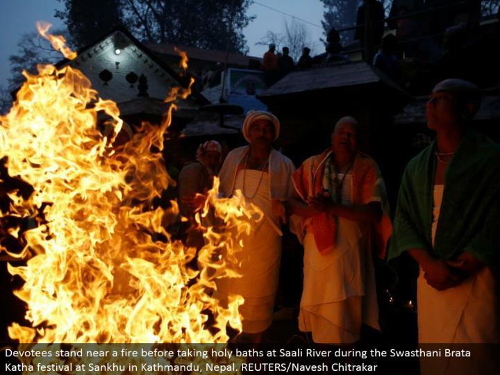 Devotees remain close to a fire before washing up at Saali River amid the Swasthani Brata Katha celebration at Sankhu in Kathmandu, Nepal. REUTERS/Navesh Chitrakar