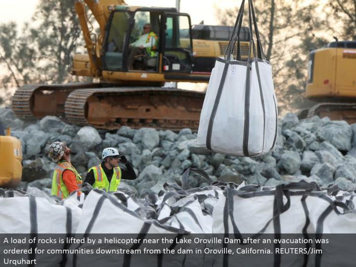 A heap of rocks is lifted by a helicopter close to the Lake Oroville Dam after a clearing was requested for groups downstream from the dam in Oroville, California. REUTERS/Jim Urquhart