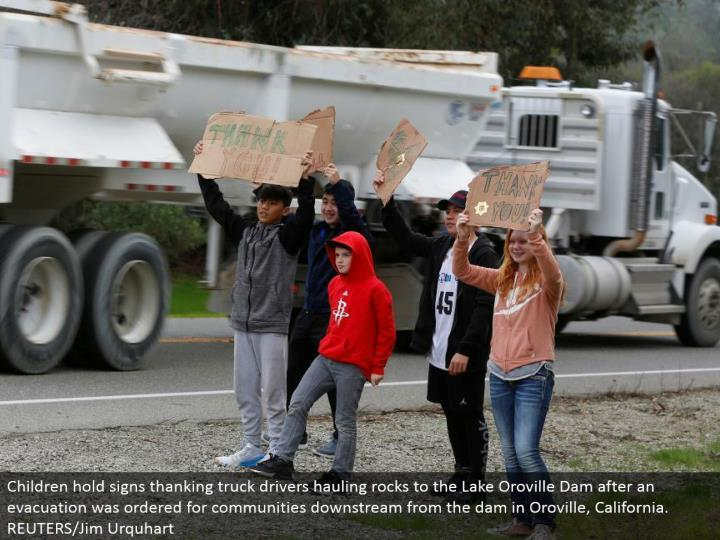 Children hold signs expressing gratitude toward truck drivers pulling rocks to the Lake Oroville Dam after a departure was requested for groups downstream from the dam in Oroville, California. REUTERS/Jim Urquhart