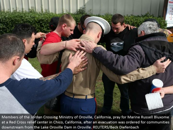 Members of the Jordan Crossing Ministry of Oroville, California, appeal to God for Marine Russell Bluxome at a Red Cross alleviation focus in Chico, California, after a clearing was requested for groups downstream from the Lake Oroville Dam in Oroville. REUTERS/Beck Diefenbach