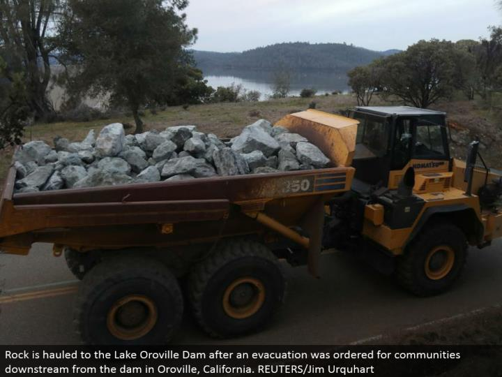 Rock is pulled to the Lake Oroville Dam after a clearing was requested for groups downstream from the dam in Oroville, California. REUTERS/Jim Urquhart