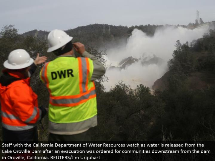 Staff with the California Department of Water Resources look as water is discharged from the Lake Oroville Dam after a departure was requested for groups downstream from the dam in Oroville, California. REUTERS/Jim Urquhart