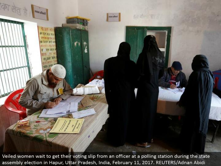 Veiled ladies hold up to get their voting slip from an officer at a surveying station amid the state get together race in Hapur, Uttar Pradesh, India, February 11, 2017. REUTERS/Adnan Abidi