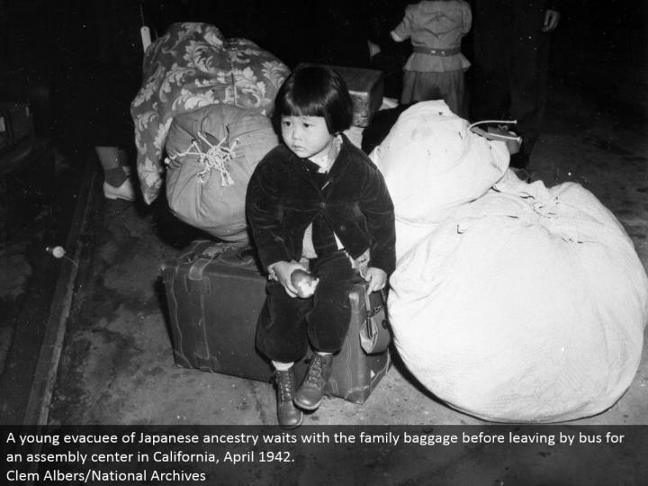 A youthful evacuee of Japanese lineage holds up with the family things before leaving by transport for a get together focus in California, April 1942. Clem Albers/National Archives