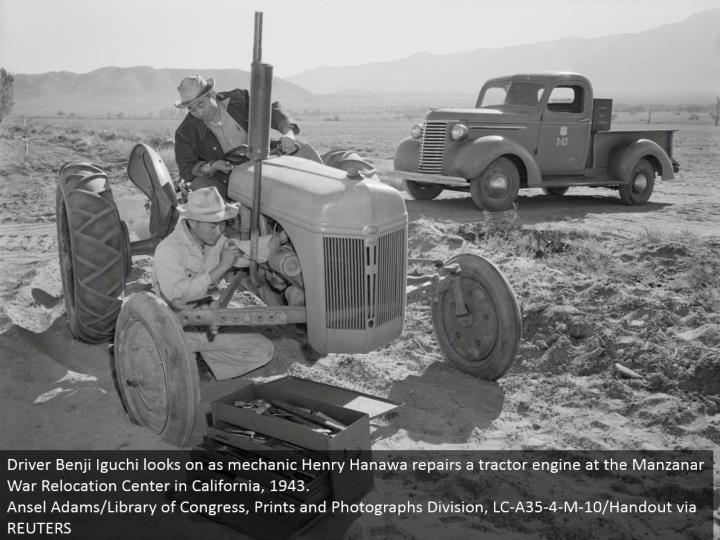 Driver Benji Iguchi looks on as repairman Henry Hanawa repairs a tractor motor at the Manzanar War Relocation Center in California, 1943. Ansel Adams/Library of Congress, Prints and Photographs Division, LC-A35-4-M-10/Handout by means of REUTERS