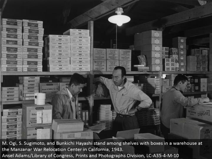 M. Ogi, S. Sugimoto, and Bunkichi Hayashi remain among racks with boxes in a distribution center at the Manzanar War Relocation Center in California, 1943. Ansel Adams/Library of Congress, Prints and Photographs Division, LC-A35-4-M-10