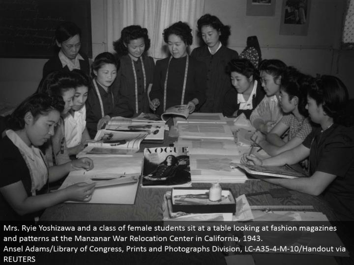 Mrs. Ryie Yoshizawa and a class of female understudies sit at a table taking a gander at design magazines and examples at the Manzanar War Relocation Center in California, 1943. Ansel Adams/Library of Congress, Prints and Photographs Division, LC-A35-4-M-10/Handout by means of REUTERS