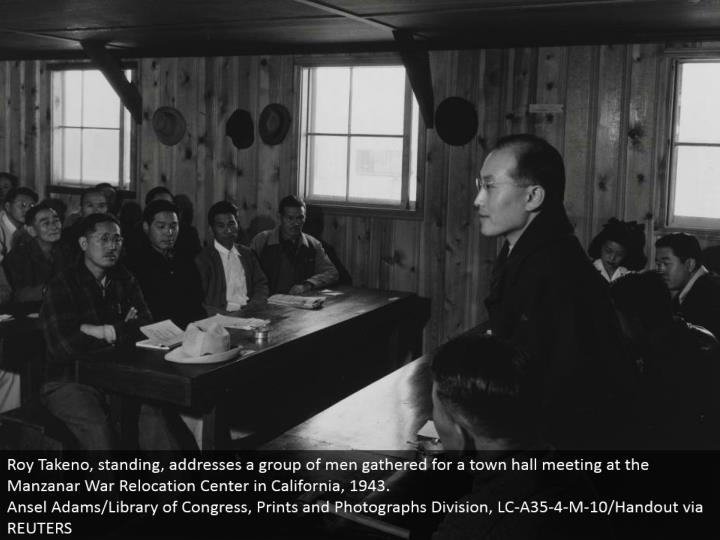 Roy Takeno, standing, addresses a gathering of men accumulated for a town lobby meeting at the Manzanar War Relocation Center in California, 1943. Ansel Adams/Library of Congress, Prints and Photographs Division, LC-A35-4-M-10/Handout by means of REUTERS