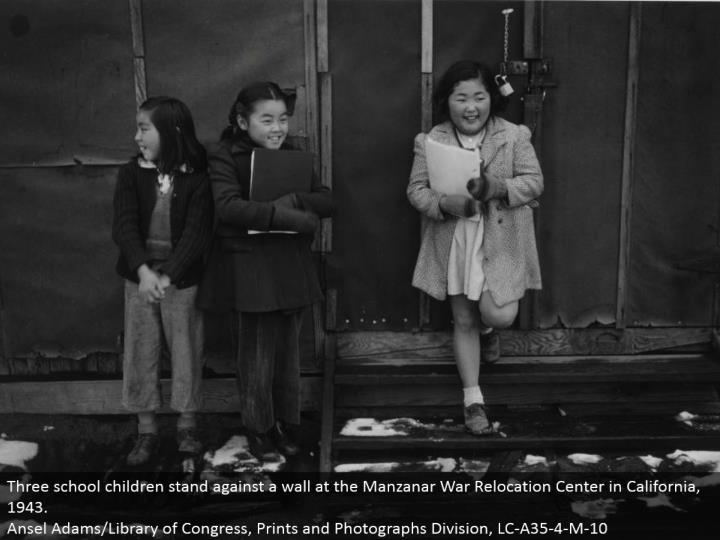 Three school youngsters remain against a divider at the Manzanar War Relocation Center in California, 1943. Ansel Adams/Library of Congress, Prints and Photographs Division, LC-A35-4-M-10