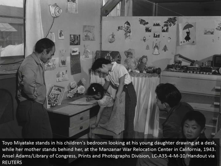 Toyo Miyatake remains in his youngsters' room taking a gander at his young little girl drawing at a work area, while her mom remains behind her, at the Manzanar War Relocation Center in California, 1943. Ansel Adams/Library of Congress, Prints and Photographs Division, LC-A35-4-M-10/Handout by means of REUTERS