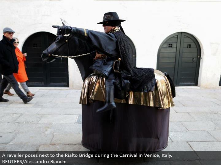 A reveler postures beside the Rialto Bridge amid the Carnival in Venice, Italy. REUTERS/Alessandro Bianchi