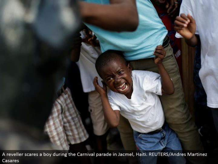 A reveler startles a kid amid the Carnival parade in Jacmel, Haiti. REUTERS/Andres Martinez Casares