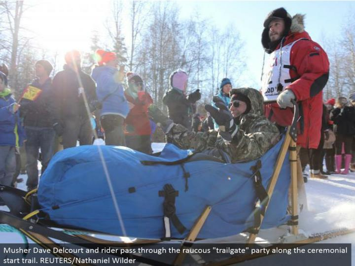 """Musher Dave Delcourt and rider go through the rambunctious """"trailgate"""" party along the stylized begin trail. REUTERS/Nathaniel Wilder"""