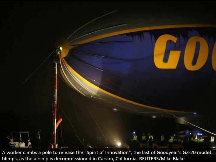 "A laborer climbs a post to discharge the ""Soul of Innovation"", the remainder of Goodyear's GZ-20 display airships, as the carrier is decommissioned in Carson, California. REUTERS/Mike Blake"