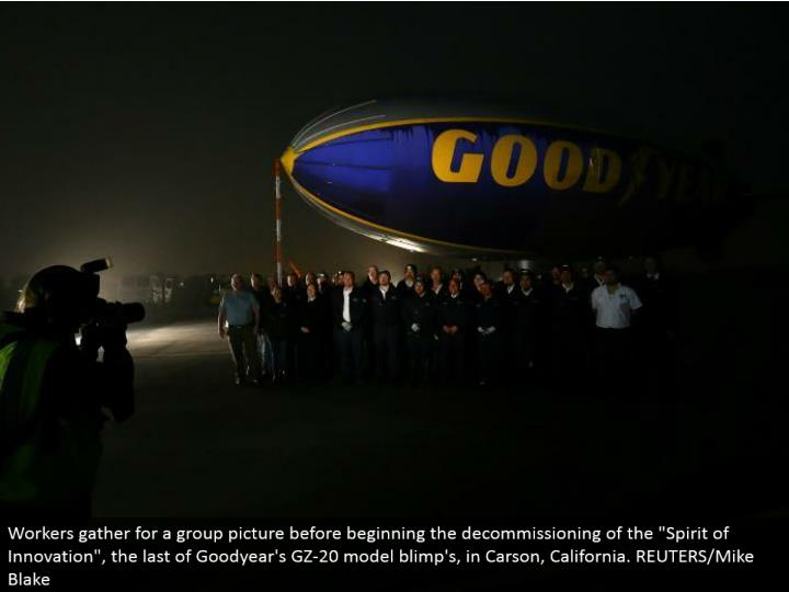 "Workers assemble for a gathering picture before starting the decommissioning of the ""Soul of Innovation"", the remainder of Goodyear's GZ-20 model blimp's, in Carson, California. REUTERS/Mike Blake"