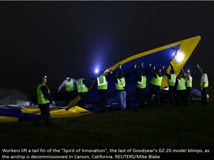 "Workers lift a tail balance of the ""Soul of Innovation"", the remainder of Goodyear's GZ-20 show zeppelins, as the aircraft is decommissioned in Carson, California. REUTERS/Mike Blake"