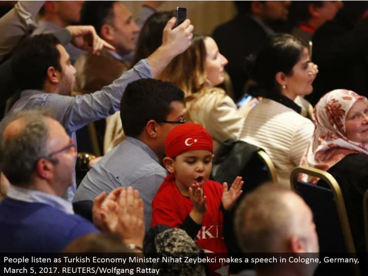 People tune in as Turkish Economy Minister Nihat Zeybekci makes a discourse in Cologne, Germany, March 5, 2017. REUTERS/Wolfgang Rattay