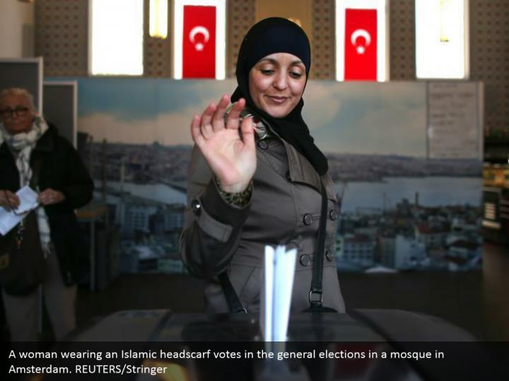 A lady wearing an Islamic headscarf votes in the general decisions in a mosque in Amsterdam. REUTERS/Stringer