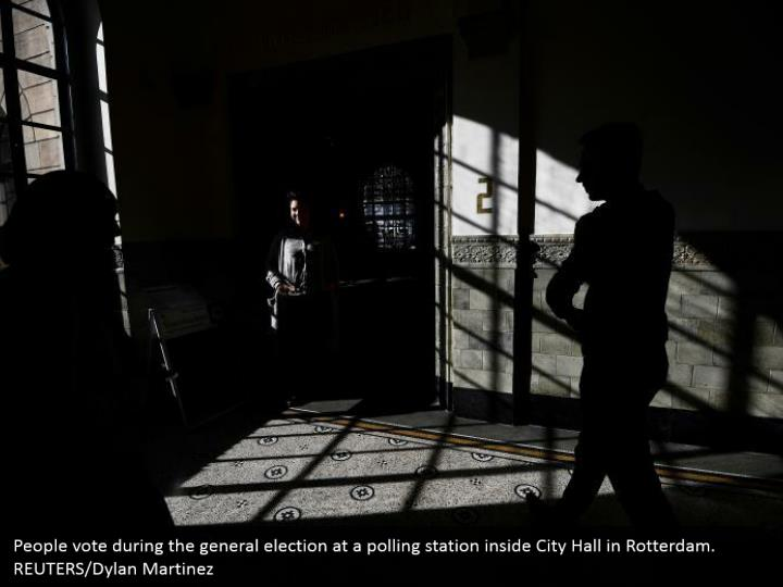 People vote amid the general race at a surveying station inside City Hall in Rotterdam. REUTERS/Dylan Martinez