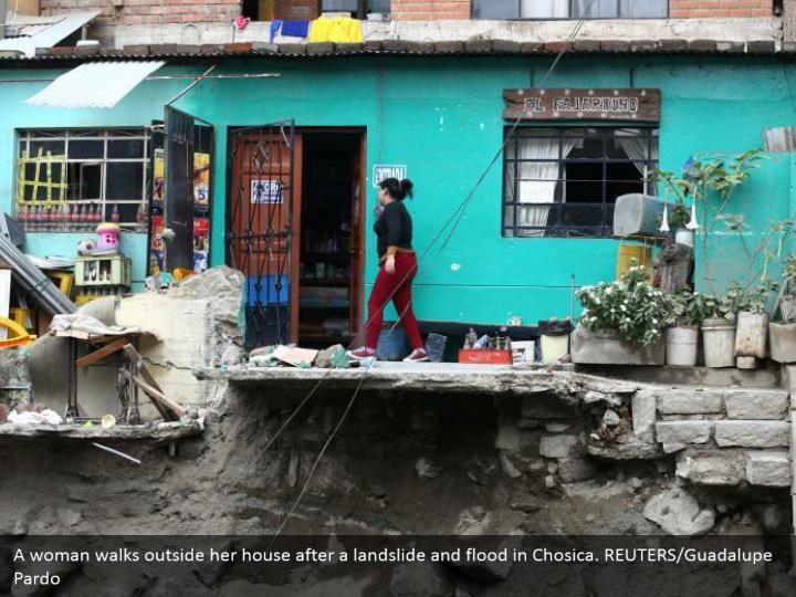 A lady strolls outside her home after an avalanche and surge in Chosica. REUTERS/Guadalupe Pardo