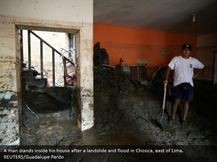 A man remains inside his home after an avalanche and surge in Chosica, east of Lima. REUTERS/Guadalupe Pardo