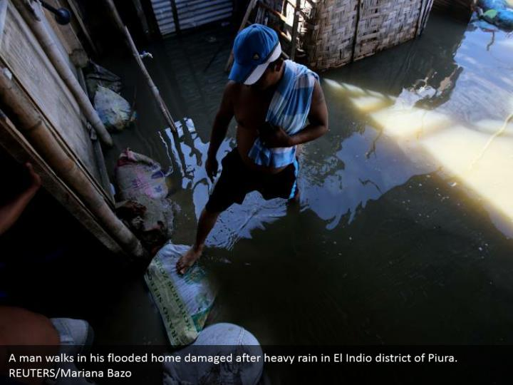A man strolls in his overflowed home harmed after substantial rain in El Indio area of Piura. REUTERS/Mariana Bazo