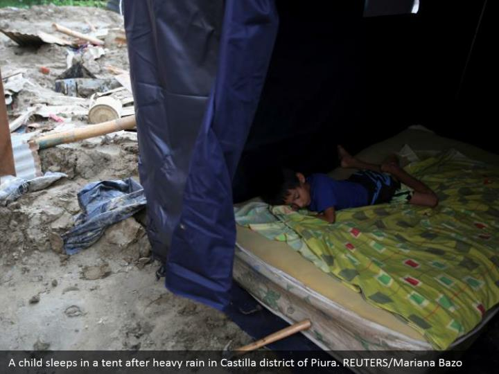 A tyke dozes in a tent after overwhelming precipitation in Castilla locale of Piura. REUTERS/Mariana Bazo
