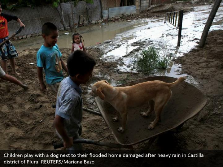 Children play with a pooch by their overflowed home harmed after substantial rain in Castilla area of Piura. REUTERS/Mariana Bazo