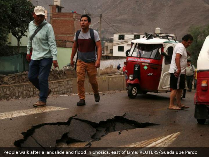 People stroll after an avalanche and surge in Chosica, east of Lima. REUTERS/Guadalupe Pardo