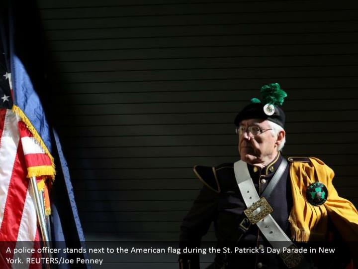 A cop remains alongside the American banner amid the St. Patrick's Day Parade in New York. REUTERS/Joe Penney