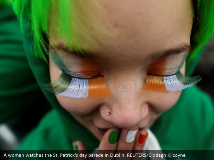 A lady watches the St. Patrick's day parade in Dublin. REUTERS/Clodagh Kilcoyne