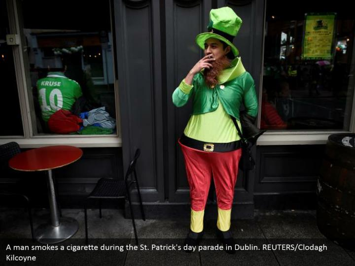 A man smokes a cigarette amid the St. Patrick's day parade in Dublin. REUTERS/Clodagh Kilcoyne