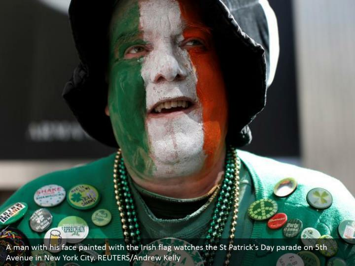 A man with his face painted with the Irish banner watches the St Patrick's Day parade on fifth Avenue in New York City. REUTERS/Andrew Kelly