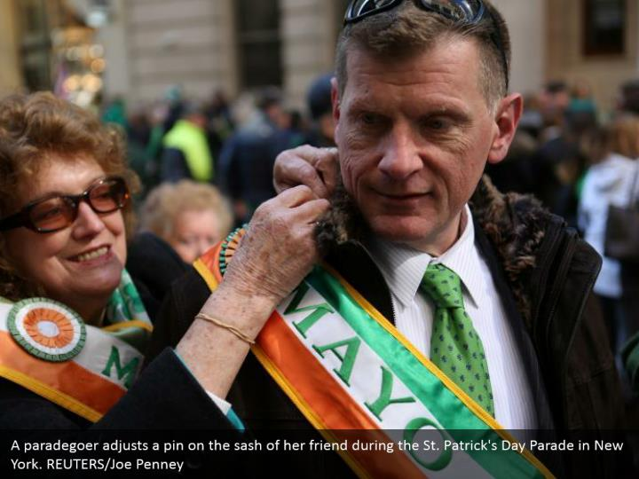 A paradegoer modifies a stick on the band of her companion amid the St. Patrick's Day Parade in New York. REUTERS/Joe Penney