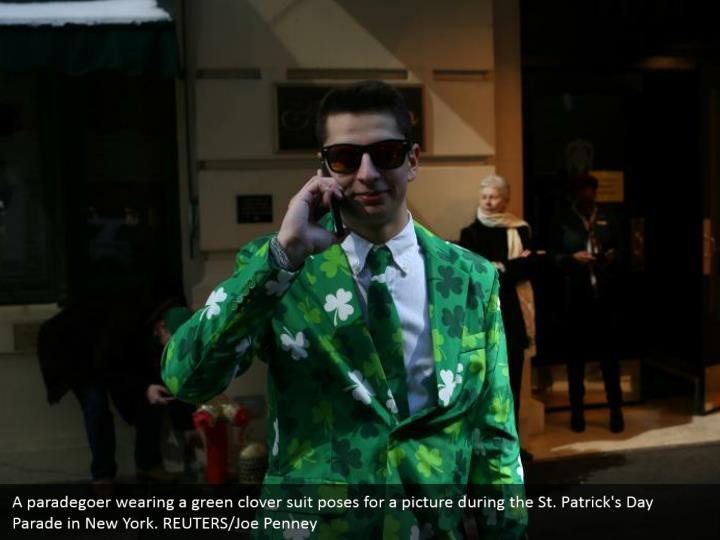 A paradegoer wearing a green clover suit postures for a photo amid the St. Patrick's Day Parade in New York. REUTERS/Joe Penney