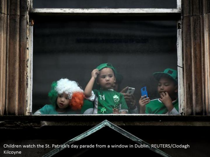 Children watch the St. Patrick's day parade from a window in Dublin. REUTERS/Clodagh Kilcoyne