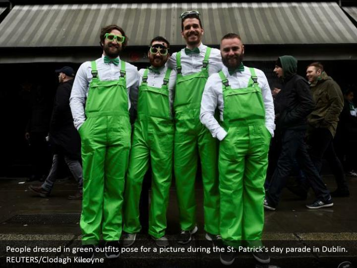 People wearing green outfits posture for a photo