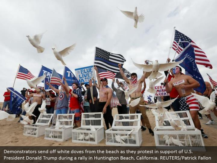 Demonstrators send off white doves from the beach as they protest in support of U.S. President Donald Trump during a rally in Huntington Beach, California. REUTERS/Patrick Fallon