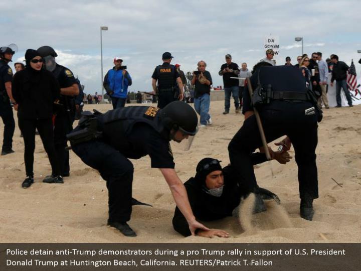 Police detain anti-Trump demonstrators during a pro Trump rally in support of U.S. President Donald Trump at Huntington Beach, California. REUTERS/Patrick T. Fallon